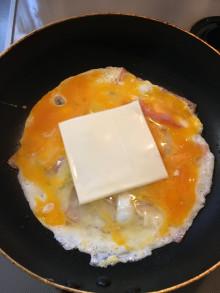 ベーコンと玉子とチーズをフライパンで焼いている