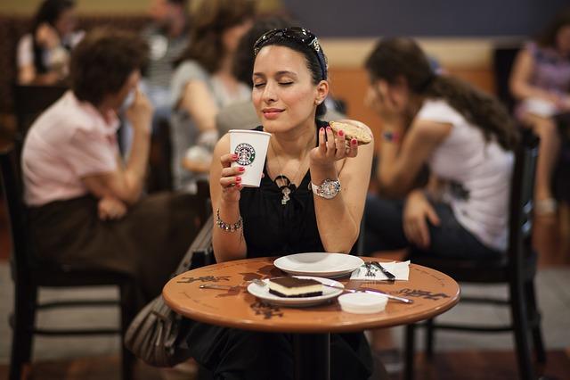 コーヒーとパンを持っている外国人女性