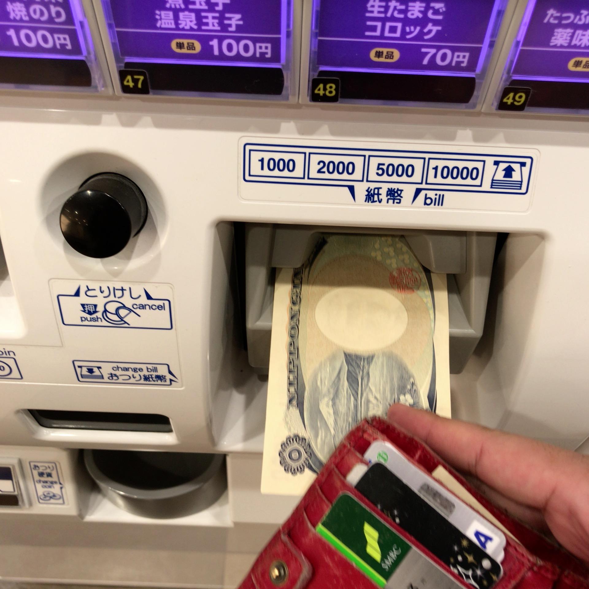券売機にお金を入れている