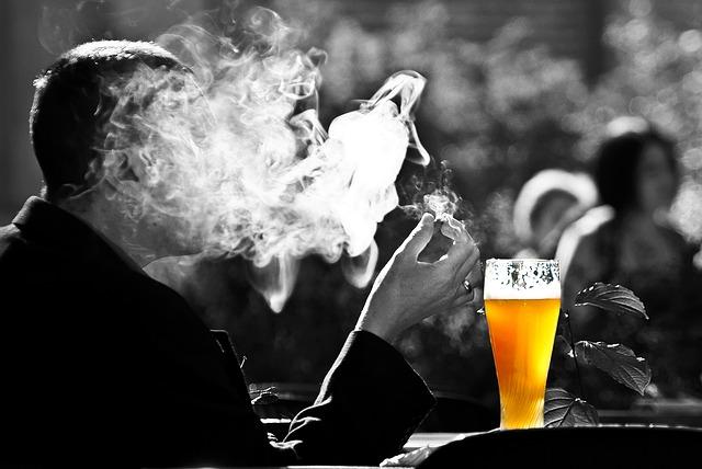 ビールを飲みながらタバコを吸っている男性
