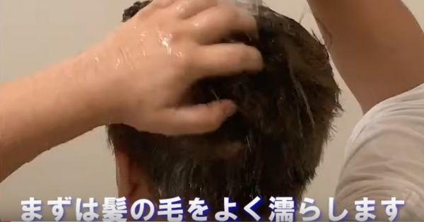 髪をシャワーで濡らしている男性