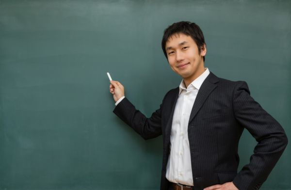 黒板の前でチョークを持っている男性