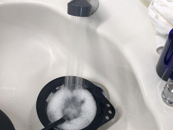 ヘアカラー用のカップと刷毛を洗っている